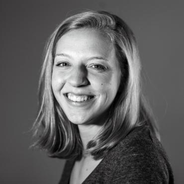 A black and white portrait of Michaela Mast smiling