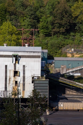 A white building that's part of a coal processing plant nestled in the trees at the bottom of a mountain. Conveyor belts on either side of the building move coal and coal dust to different parts of the plant.