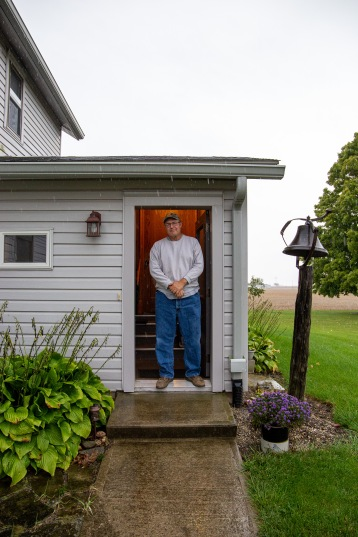 Farmer Dave Moser stands in the doorway to his home in Bluffton, Ohio. It was raining the day we interviewed Dave, keeping him from working out in the fields.