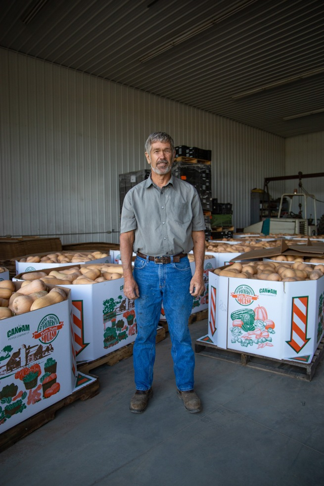 Bob stands with the most recent harvest of butternut squash from his farm.