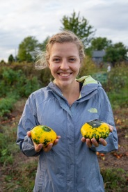 Shifting Climates host Michaela Mast helps harvest gourds and other veggies between interviews.
