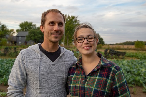 Jonah Agner and Nancy Corle Agner, members of the cooperative, stand in front of the vegetable fields on Bucksnort Farm.