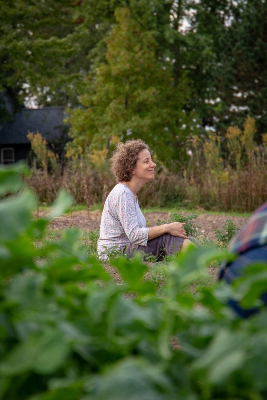 Maya Fischhoff, a member of the cooperative, sits in between rows of carrots, weeding.