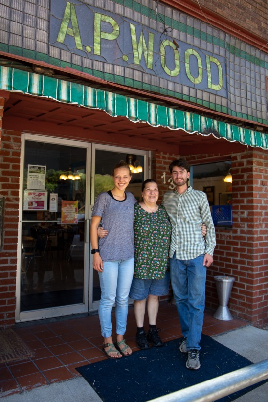 Podcast hosts Michaela Mast and Harrison Horst stand outside with owner Markella Gianato.