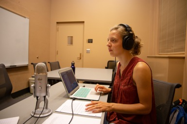 Michaela Mast, producer and co-host, sets up the microphone and checks audio in preparation for interview with Matthew Groves.