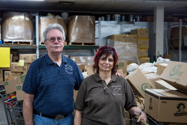Bob and Linda stand with carts of food ready for distribution.