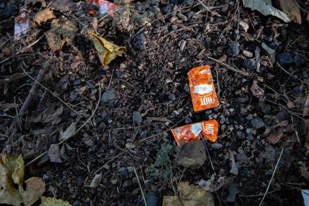 Hot sauce packets seen at an illegal dump site.
