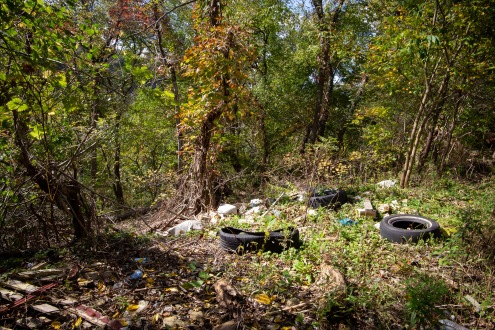 Tires, construction materials, and other types of trash thrown over a hillside.