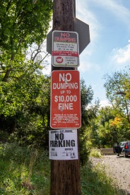 Signs stating the consequences for illegal dumping don't prevent people from adding to the waste piles in Gershon.