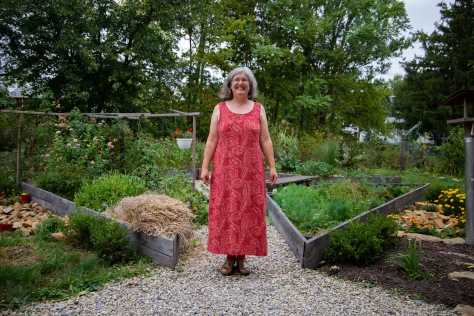 Wendy stands in front of her vibrant backyard garden.
