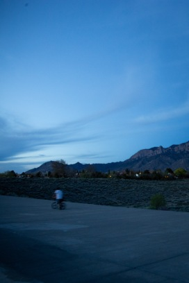 A man teaches his son to ride a bike at dusk. We sometimes talk about the desert as a place that lacks color, but in Albuquerque rich shades of blue and red cover the mountains and the sky day and night.