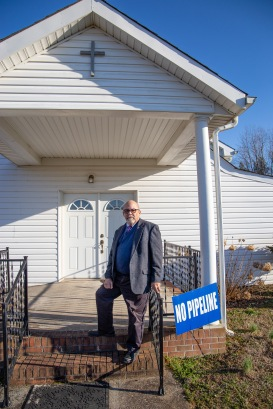 Pastor Paul stands on the front stoop of Union Grove Baptist Church. Because of his stance against the pipeline, some church members have asked for his removal, but he has remained strong and outspoken in his views on the issue.