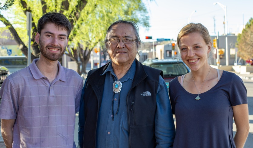 Podcast hosts Harrison Horst and Michaela Mast stand with Chief Robert Yazzie. Chief Yazzie is a renowned author of several books on Navajo Peacemaking and traditional forms of law. He was a lawyer for many years before serving as a chief justice--now he teaches at a University in Gallup, NM.